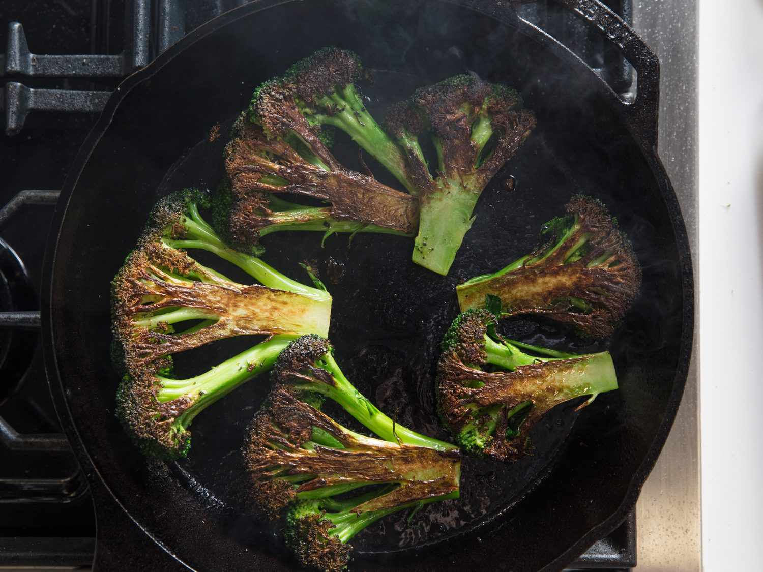 Overhead shot of charred broccoli pieces cooking in a cast iron skillet.