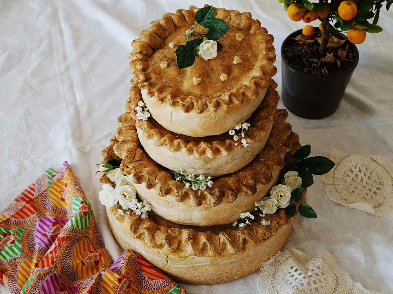 A four-tiered pork pie for a wedding, decorated with flowers