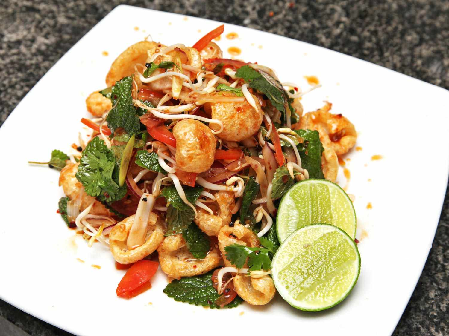 A Thai-style salad of fried pork rinds, herbs, bean sprouts, and peppers, garnished with lime halves