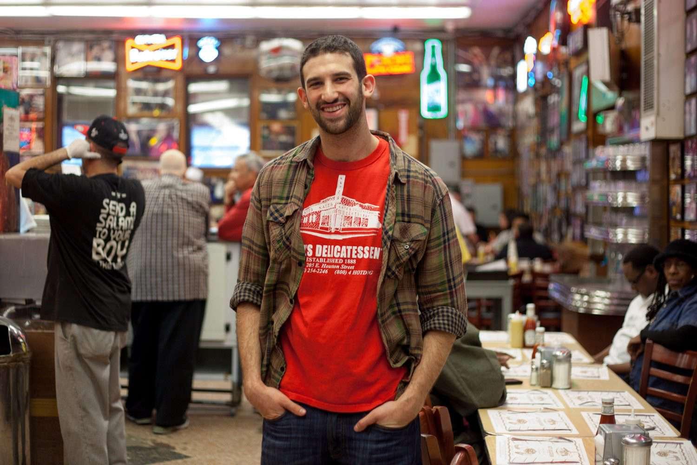 Jake Dell of Katz's posing in middle of restaurant.
