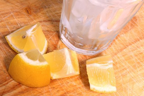 Overhead photo of ice in glass next to lemon wedges on wooden surface.