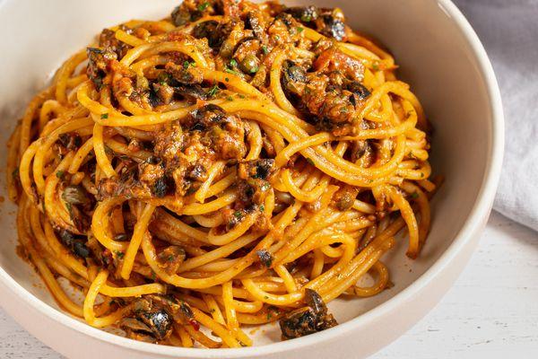 Pasta puttanesca, made with spaghetti, in a white bowl.
