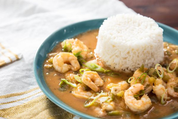 A bowl of shrimp etouffee, with a mound of white rice in the bowl.
