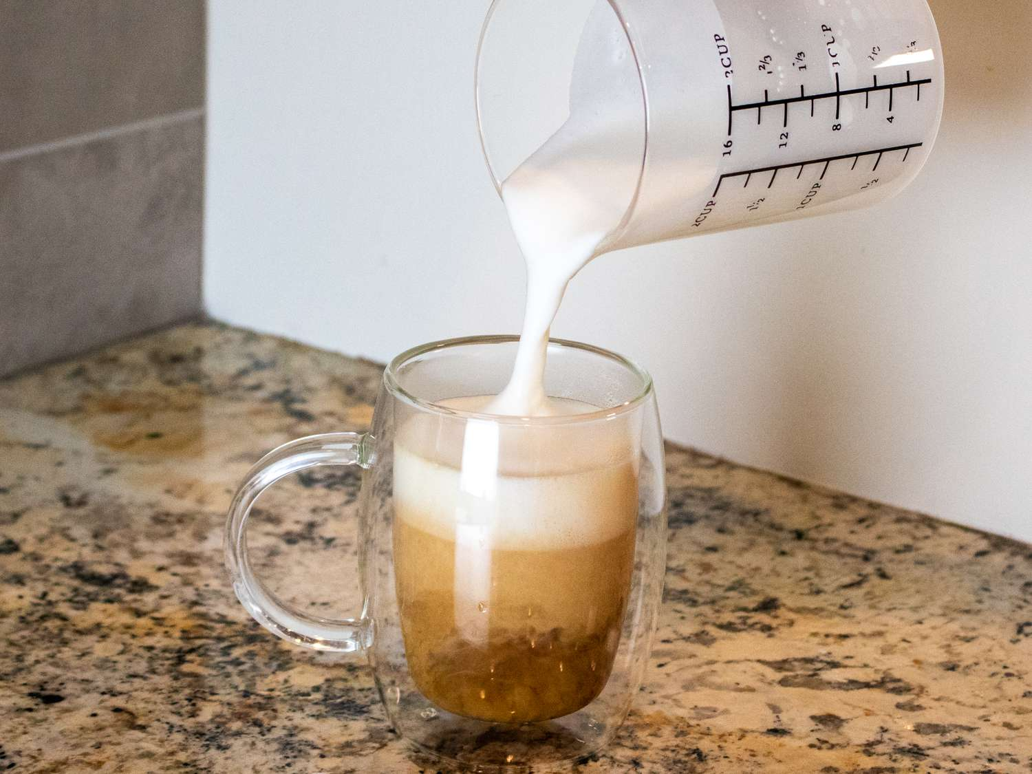 topping a coffee with foamed milk from the Miroco frother