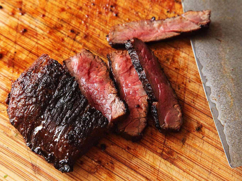 Slicing skirt steak carne asada against the grain on a wooden cutting board.