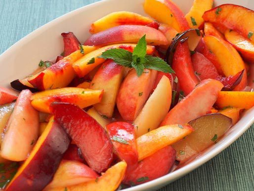 an oval casserole full of sliced peaches, plums and other stone fruit