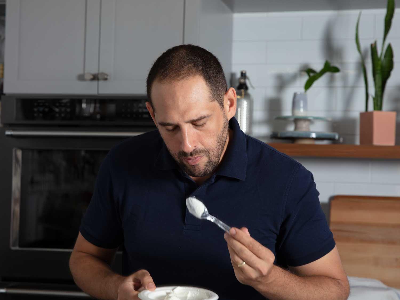 Daniel inspects a spoonful of Greek yogurt.