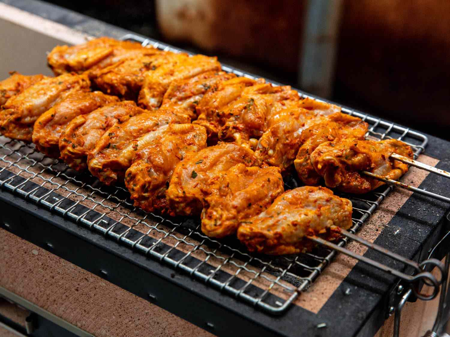 Turkish-style wings that have just begun to cook on top of a mesh wire rack on a Japanese konro charcoal grill