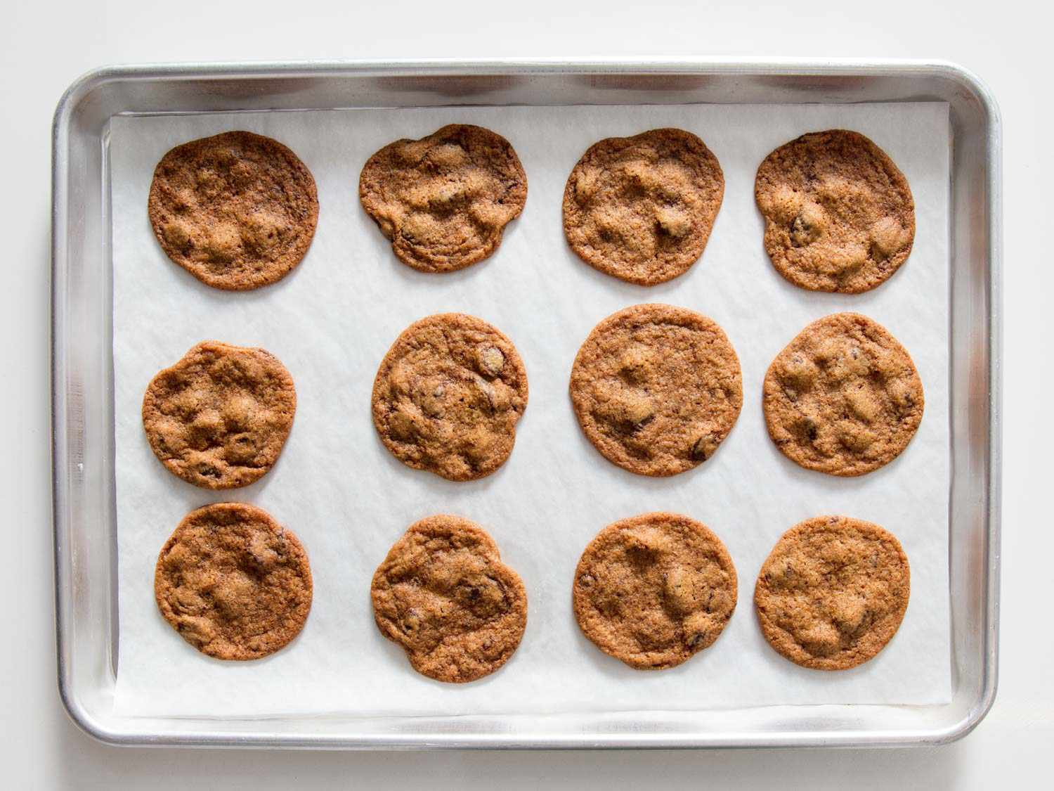 Overhead view of baked thin chocolate chip cookies on a lined rimmed baking sheet