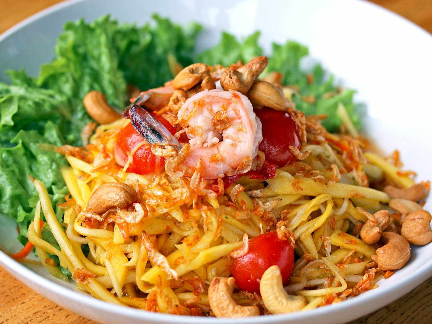 A plate of green-mango salad (tam muk muang) with shredded green mango, cashews, shrimp, tomatoes, and lettuce leaves in the background