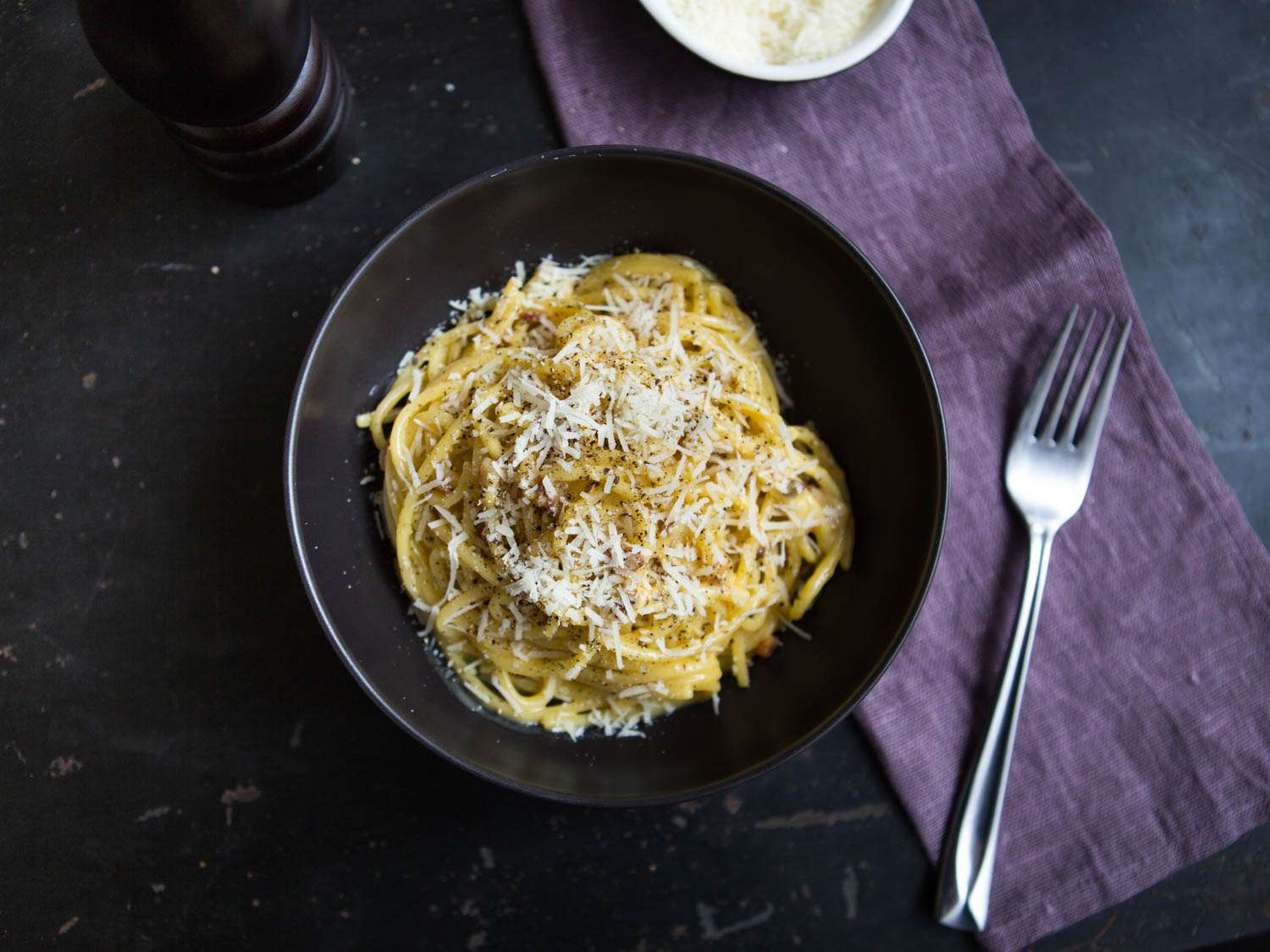 Bowl of cheese-topped spaghetti carbonara on a dark background with purple napkin.