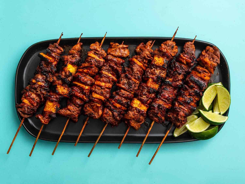 Overhead shot of grilled al pastor skewers on a serving platter with lime wedges