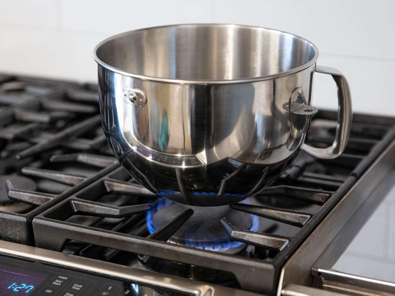 Bowl of Kitchenaid stand mixer heating up on a stovetop burner