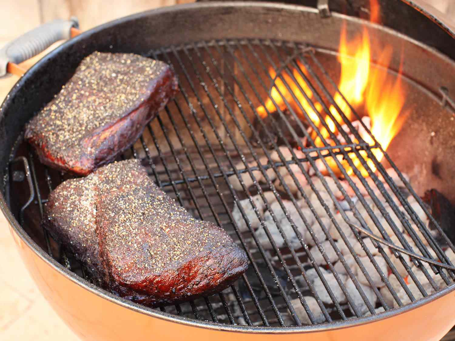 Brisket halves cooking on a charcoal grill
