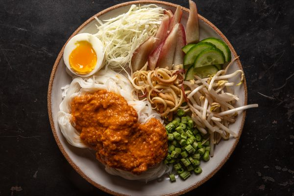 Overhead of a serving plate of noodles dressed with fish curry, with assorted vegetable garnishes and a soft-cooked egg on the side.