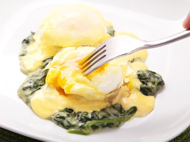 A white plate with eggs sardu--eggs Benedict on top of creamed spinach and artichoke hearts, topped with hollandaise sauce.