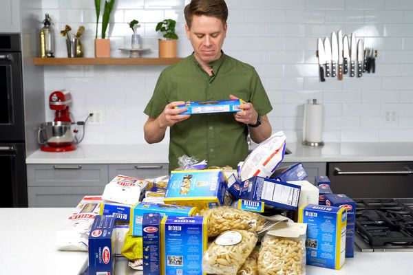 Sasha Marx from Serious Eats standing in a kitchen with a pile of different packages of pastas on the counter in front of him.