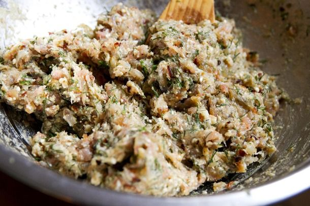 A wooden spoon mixing ground chicken with seasonings and dill in a metal bowl