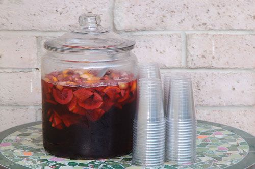 A large jar of red sangria on a table, next to stacks of plastic cups.