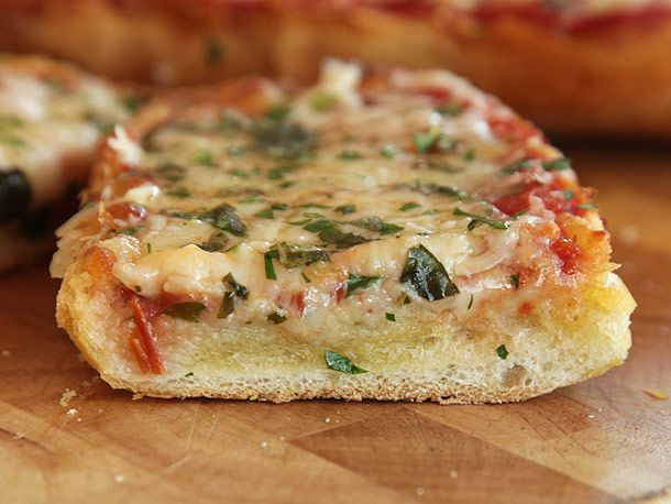Close up of French bread pizza finished with cheese and herbs.