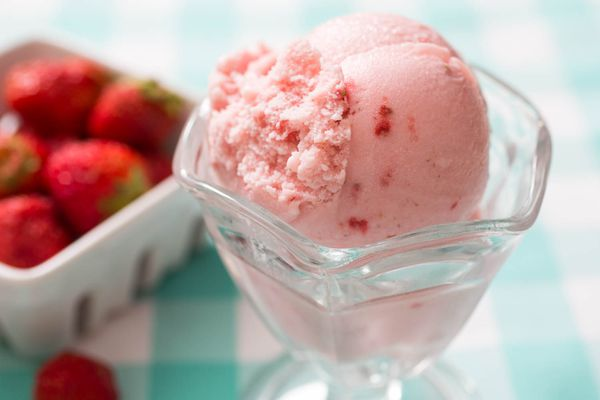 A scoop of homemade strawberry ice cream in a sundae glass. A small basket of fresh strawberries is in the background.