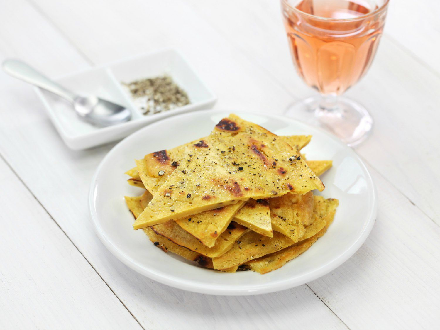 Wedges of socca, a farinata pancake, on a small white plate with a glass of rose wine next to it.