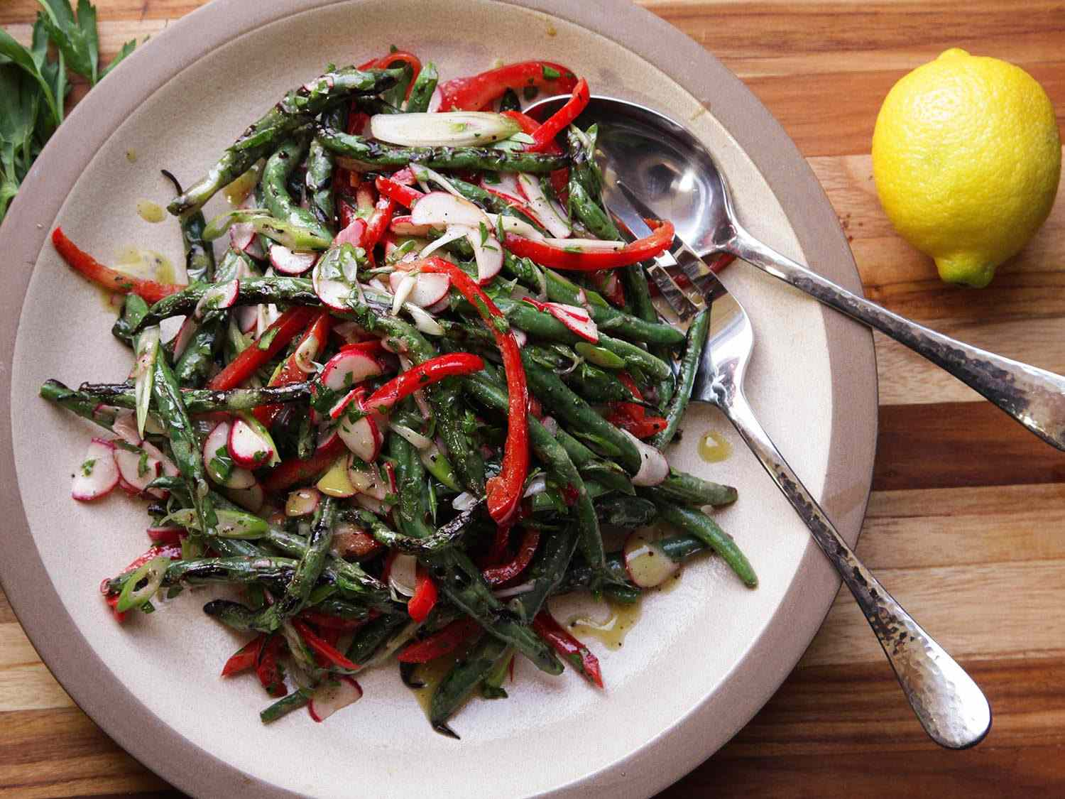 Overhead shot of a ceramic plate of Grilled Green Bean Salad With Red Peppers and Radishes