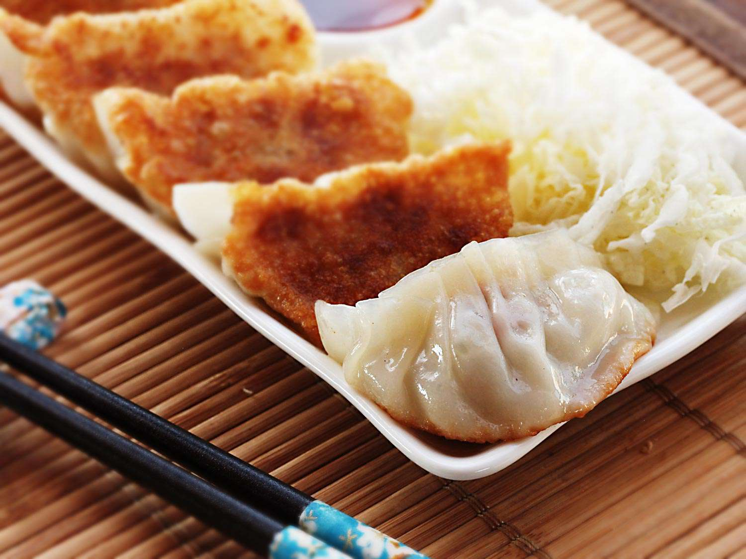 A platter of five pork and cabbage gyoza. Four of the dumplings are positioned crisp side facing up, and one dumpling is crisp-side down. A pair of chopsticks is next to the platter.