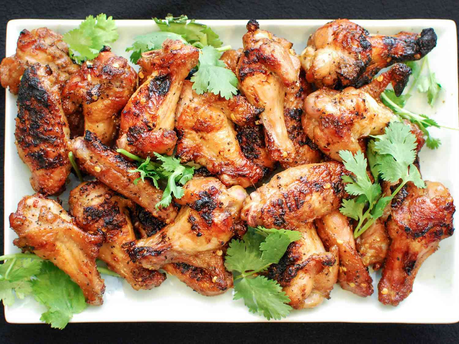 Overhead shot of a platter of grilled chicken wings with soy and fish sauce, garnished with cilantro leaves