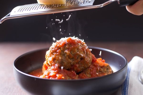 Italian American-style meatballs in a bowl with tomato sauce. Someone is grating parmesan cheese over the meatballs.
