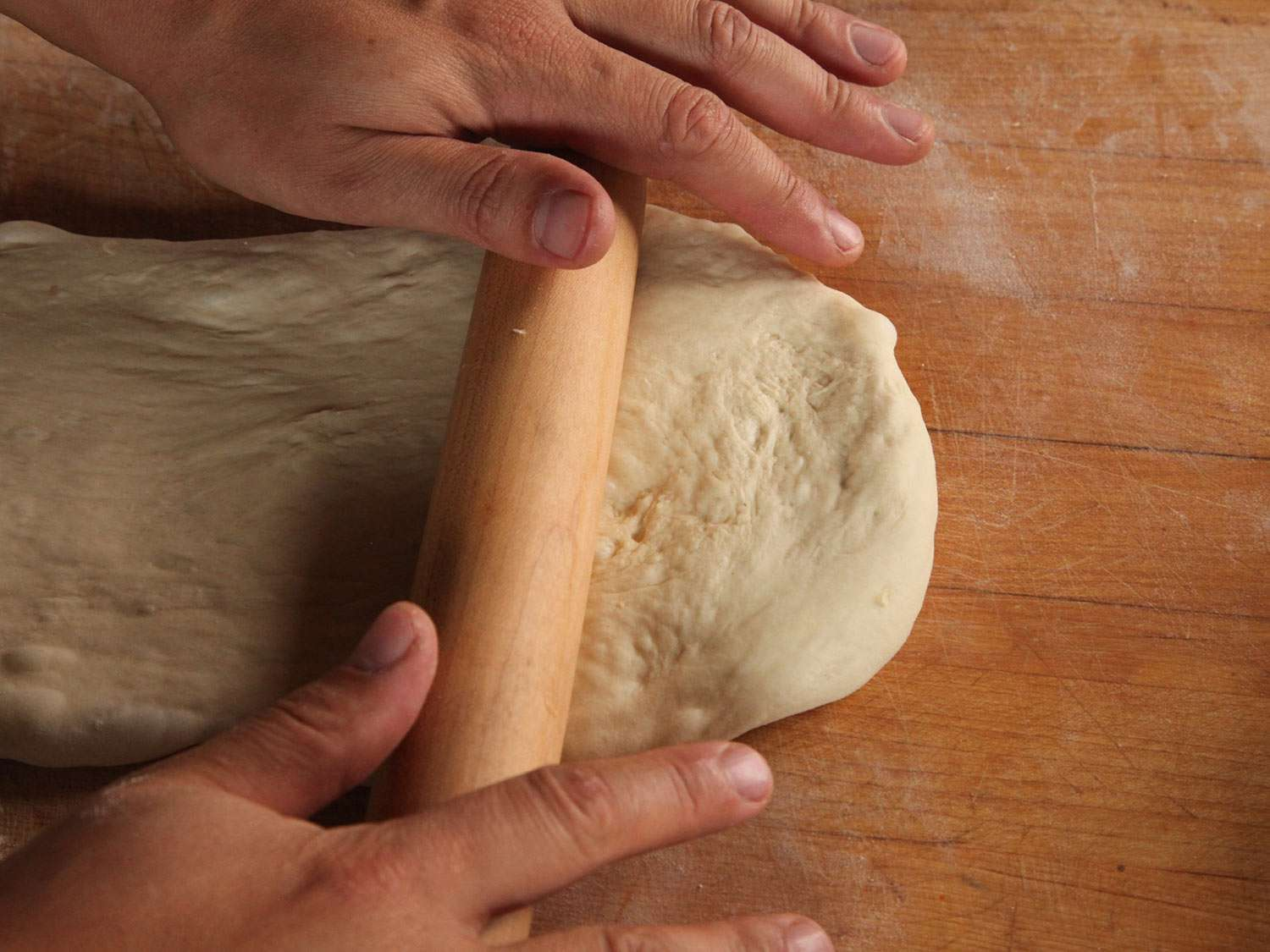 A pair of hands using a rolling pin to roll out dough on a wooden surface
