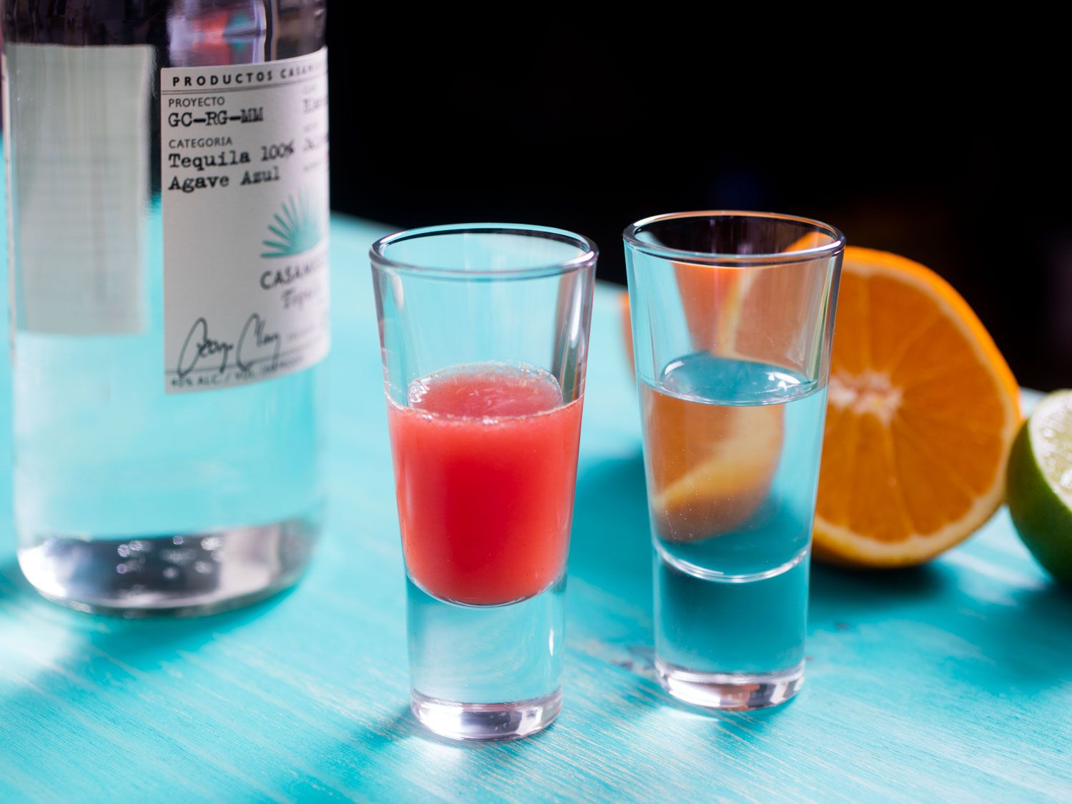 A shot glass of pomegranate, orange, and chili sangrita, next to a shot glass of tequila, with orange and lime in the background