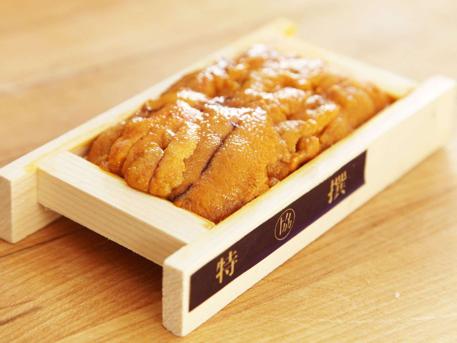 A wooden tray of fresh orange uni (sea urchin roe) on a wooden surface