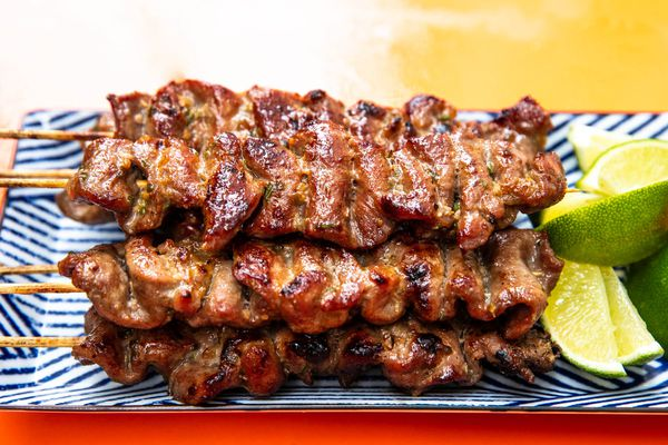 Thai-style grilled pork skewers on a rectangular platter with lime wedges