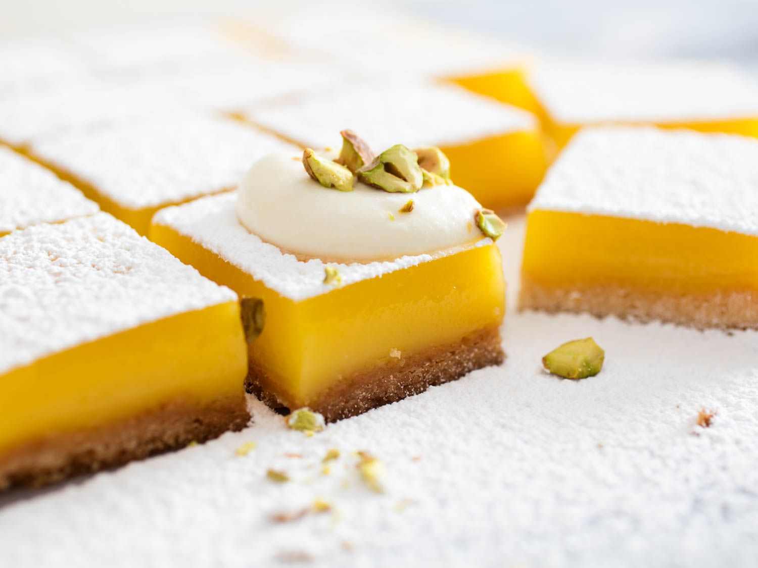 Lemon bars topped with powdered sugar, lemon chantilly, and chopped candied pistachios.