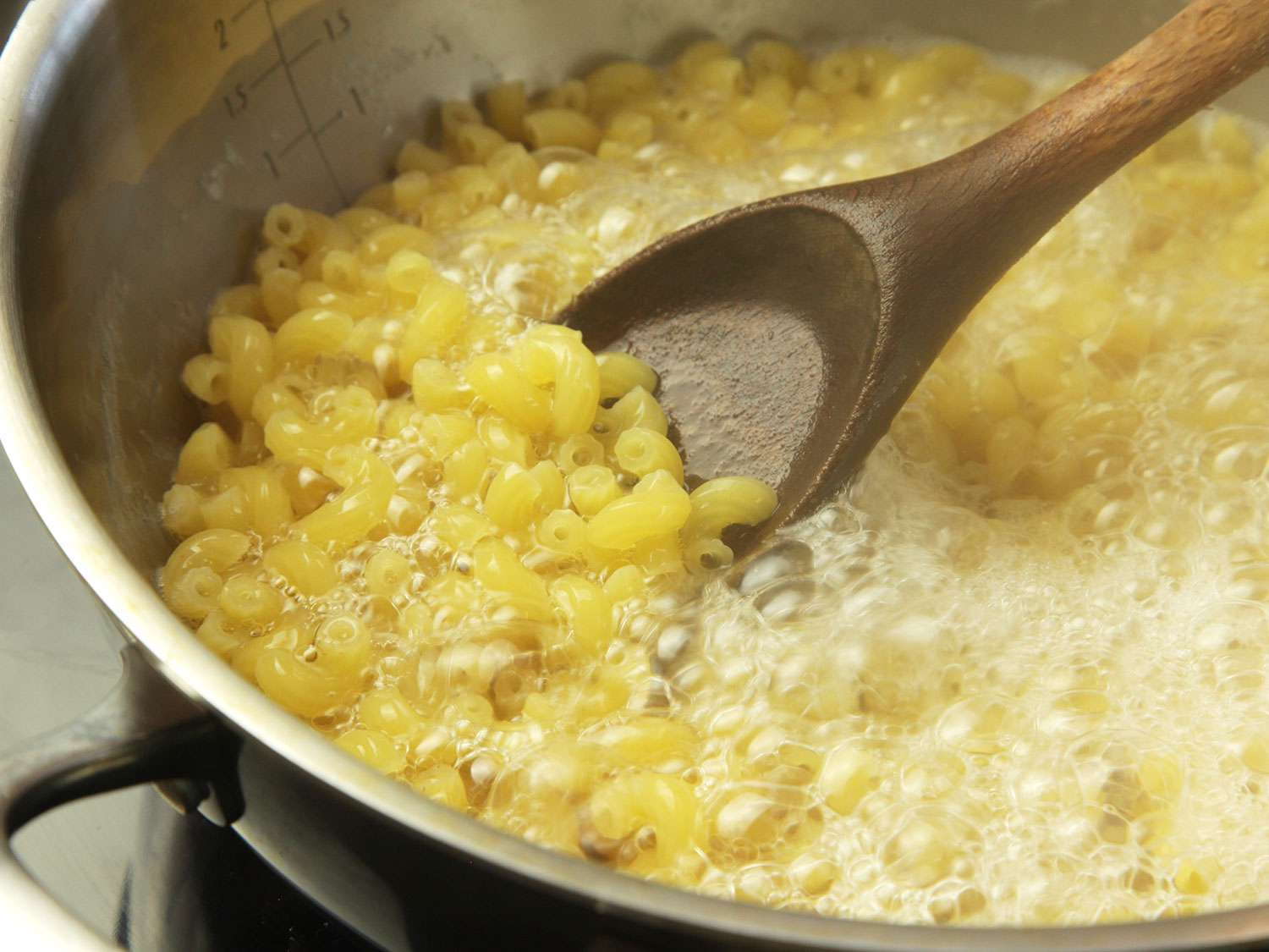 Macaroni in a boiling pot of water, being stirred. There is only just enough water to cover the pasta, which helps concentrate starch.