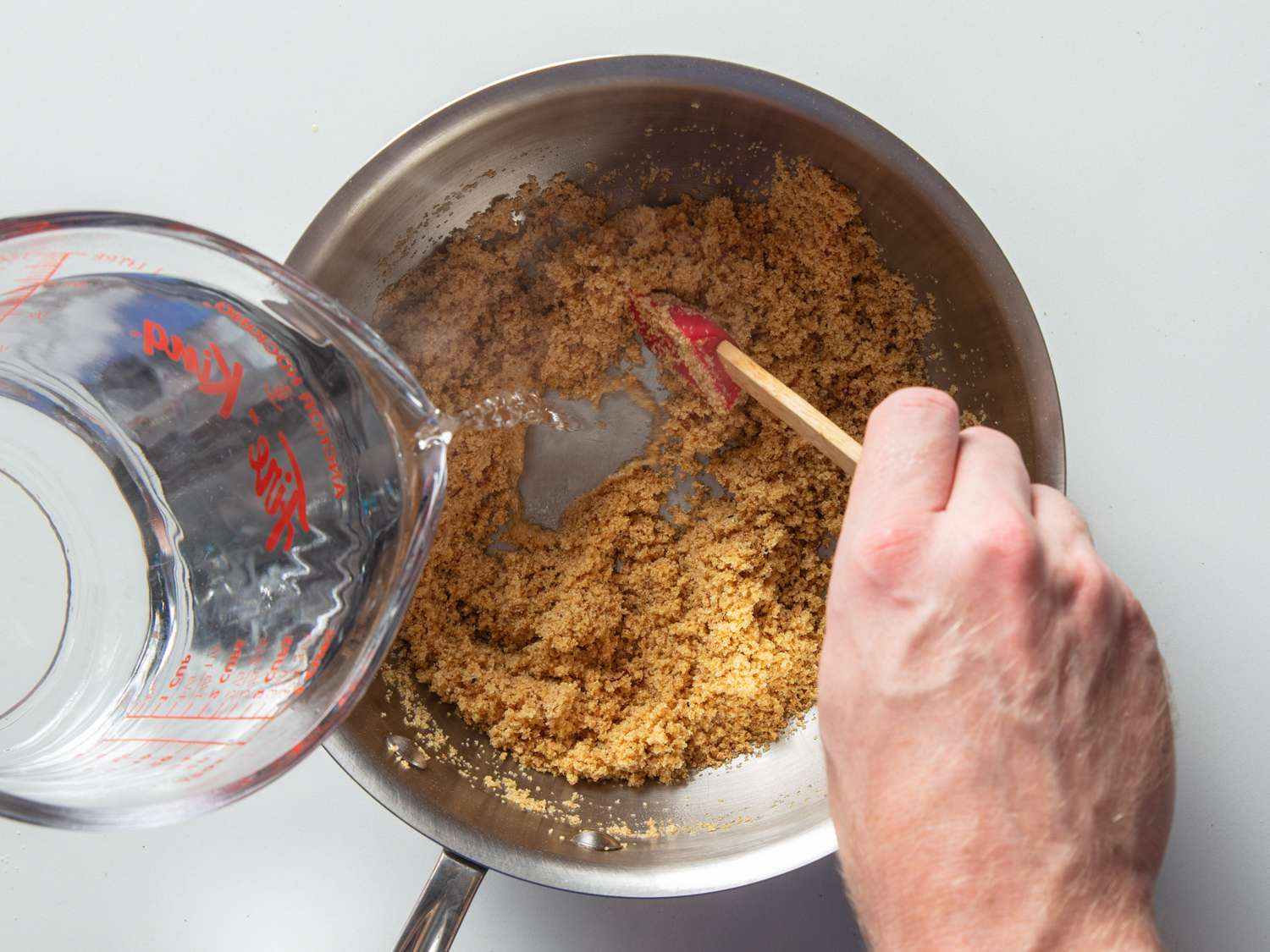 Boiling water being poured into a saucepan containing a mixture of semolina and ghee