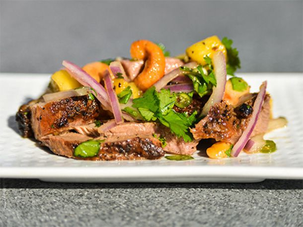 A salad of grilled duck mixed with pineapple chunks, red onion, cashew, and cilantro