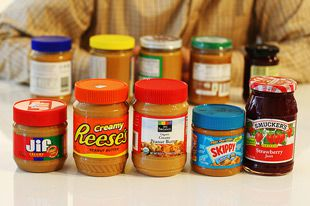 An assortment of different brands of peanut butters and jellies in jars on a table.