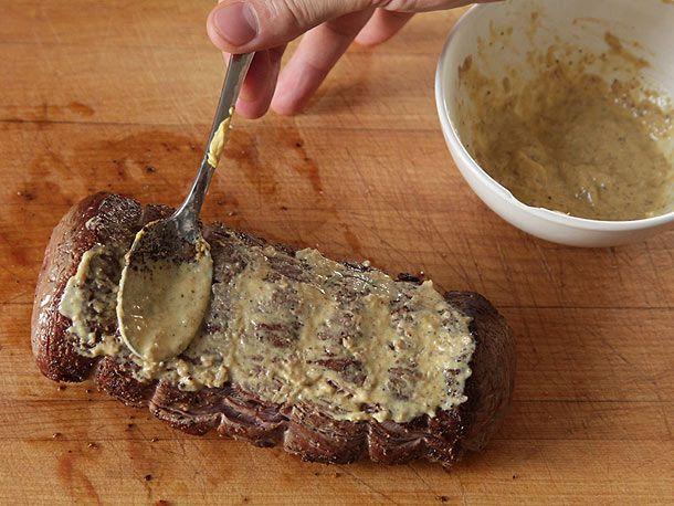Spreading mustard on a seared beef tenderloin for beef Wellington.