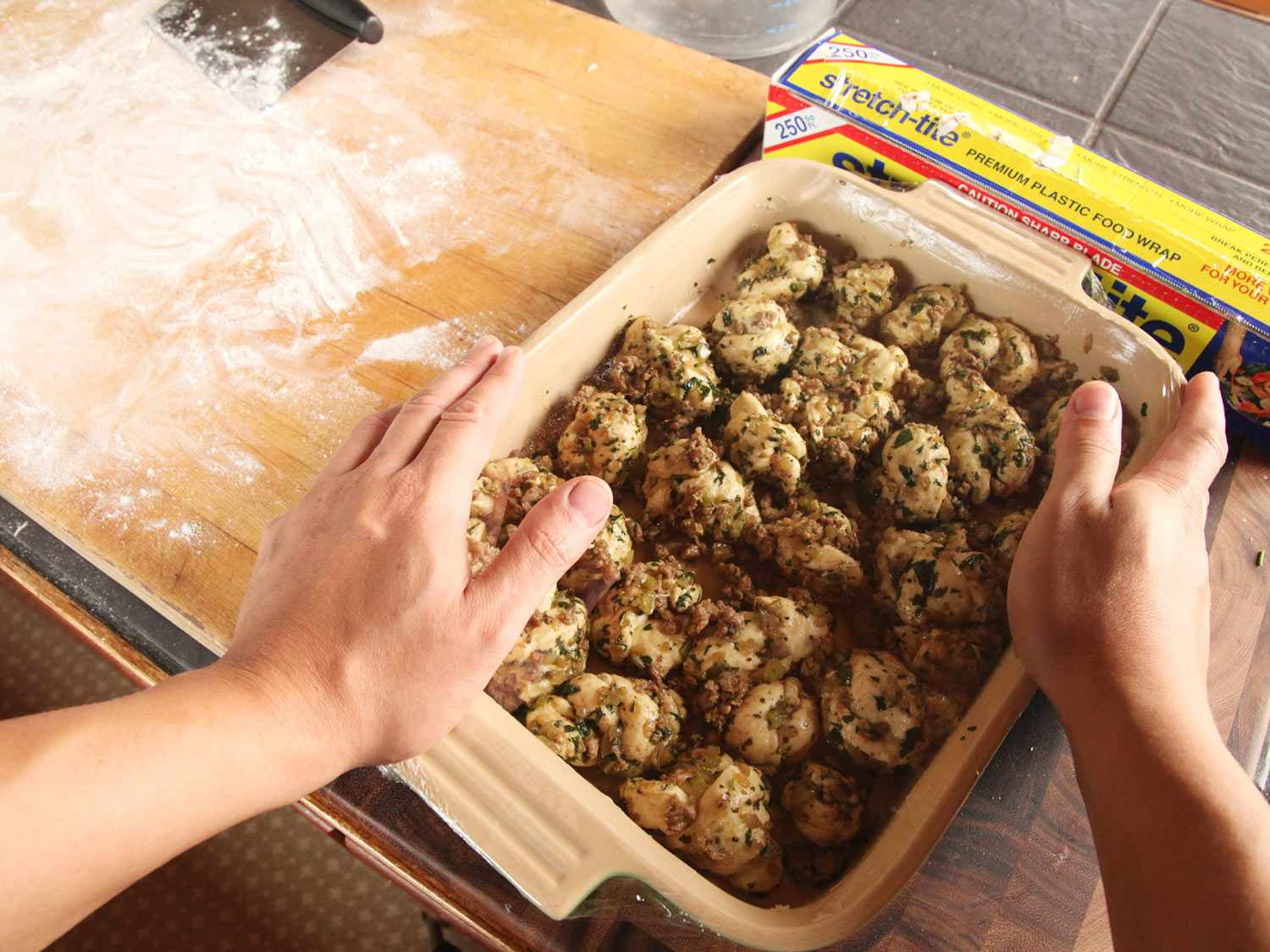 Hands framing a baking dish full of unbaked pull-apart stuffing rolls, next to a box of plastic wrap