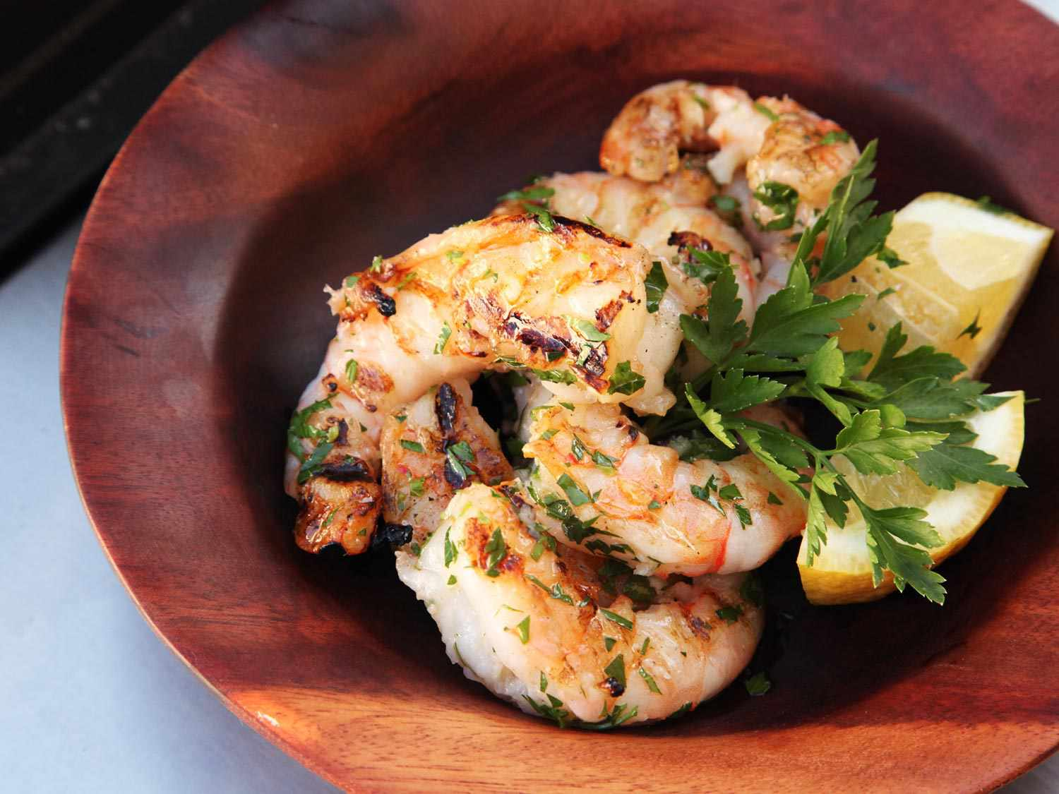 Grilled shrimp with garlic and lemon, sprinkled with herbs, in a wooden dish