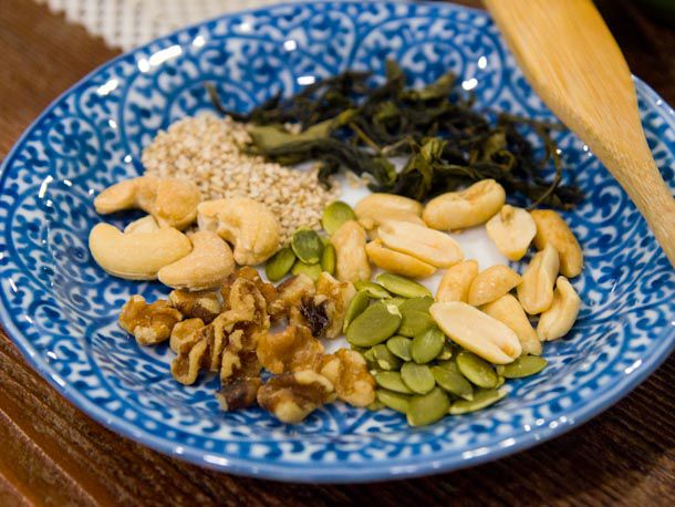 nuts, seeds, and tea leaves on a blue plate
