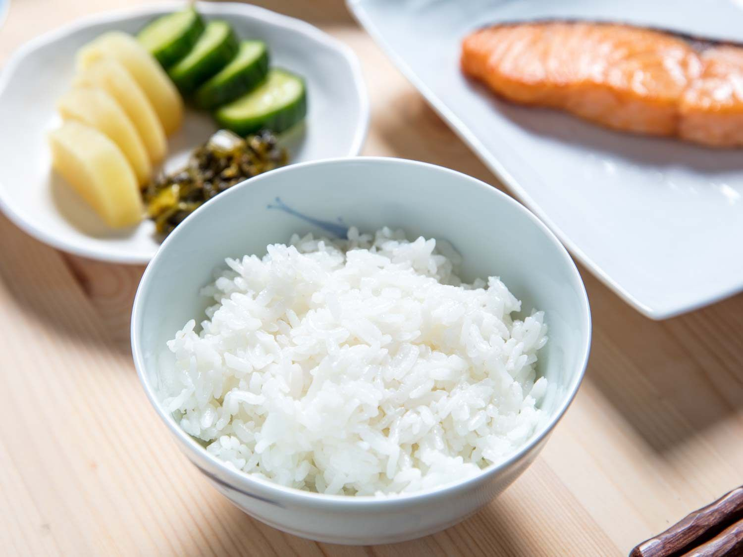 A ceramic bowl of white rice, with pickles and salted salmon in the background