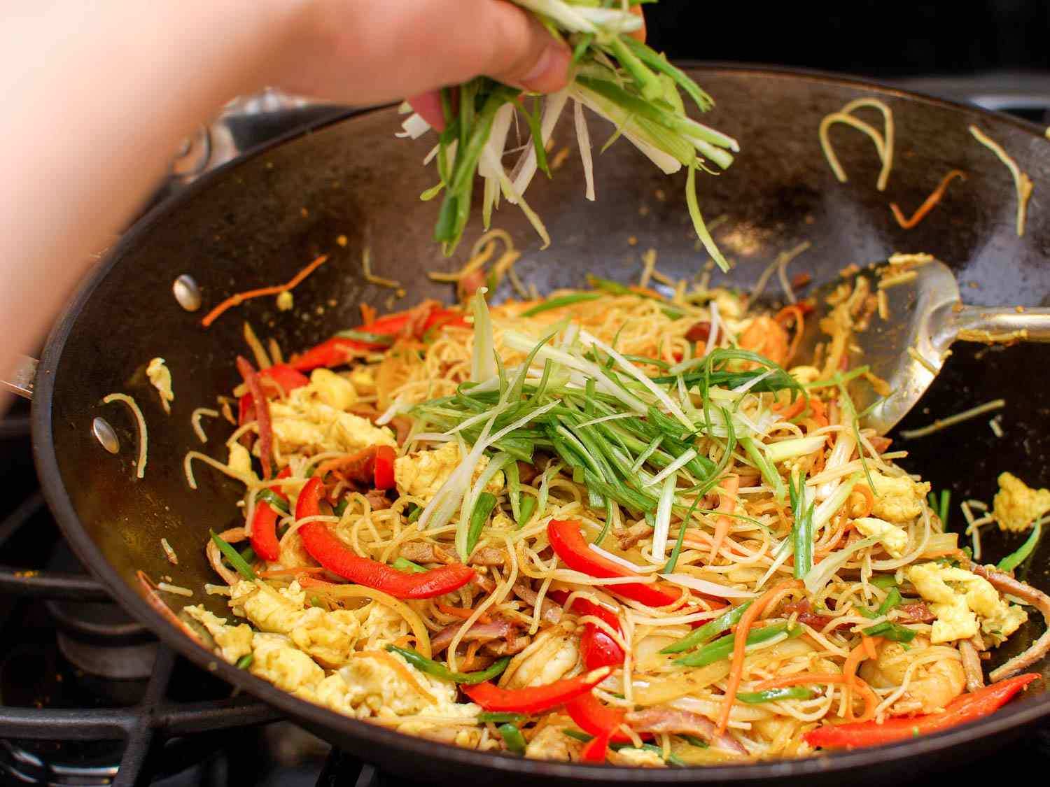 A hand sprinkling sliced scallions into wok of Singapore rice noodles.
