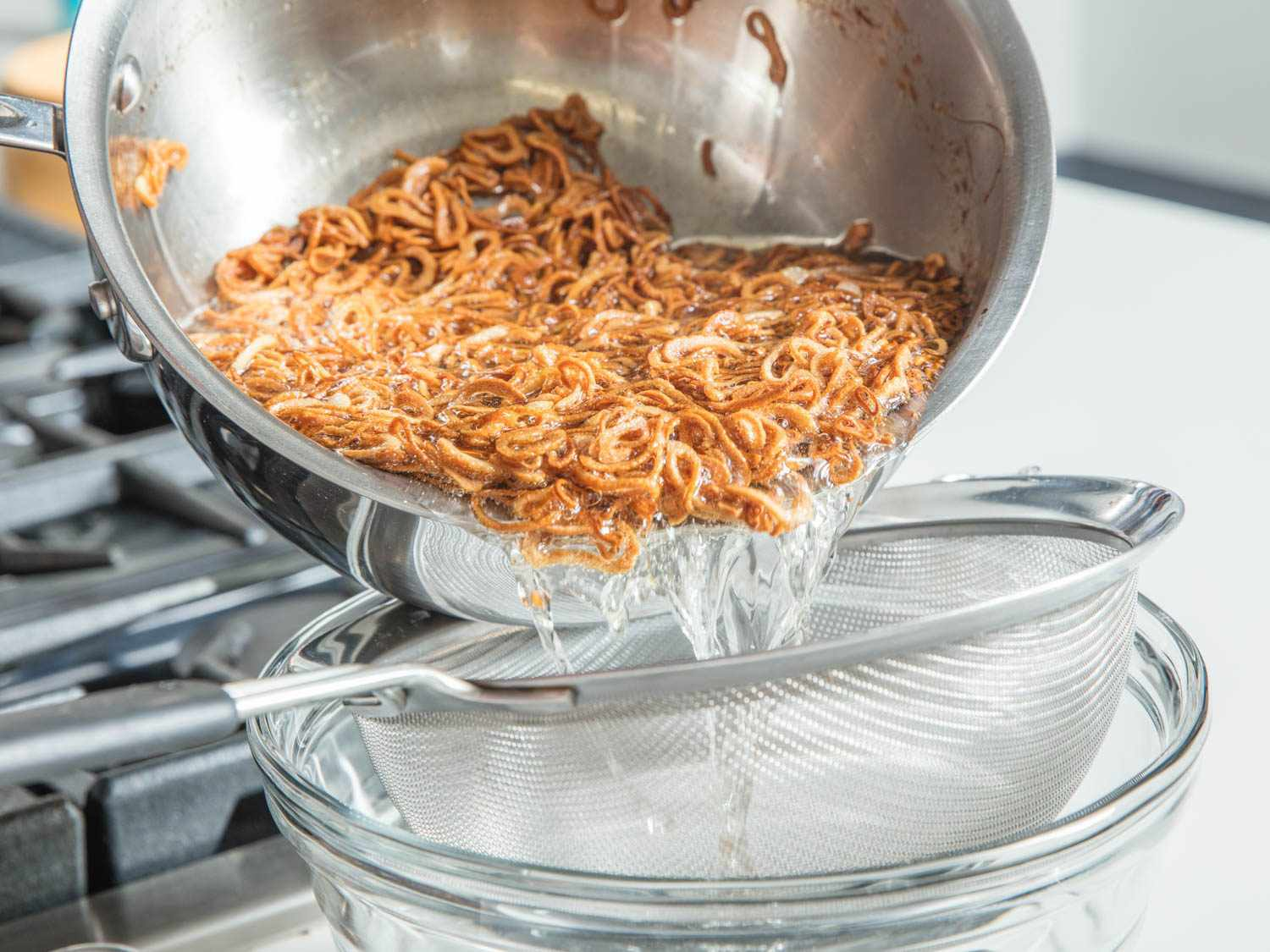 Draining fried shallots in a fine-mesh strainer over a heat-proof bowl.