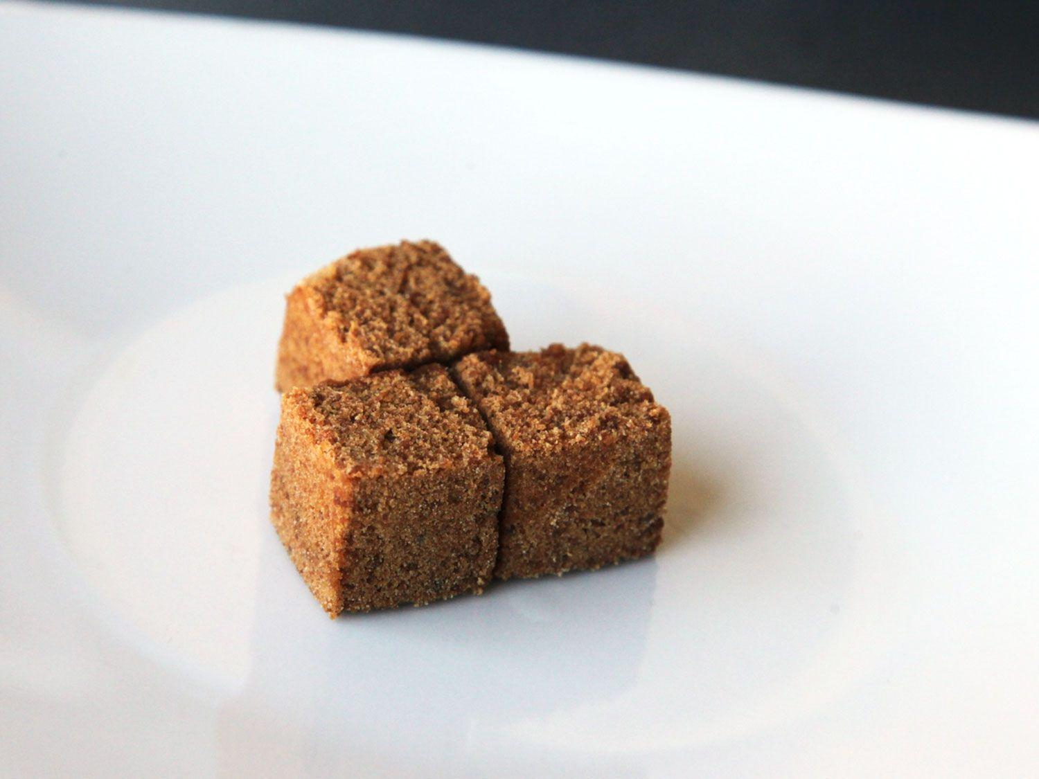 Panela (evaporated cane juice) cubes on a white plate.