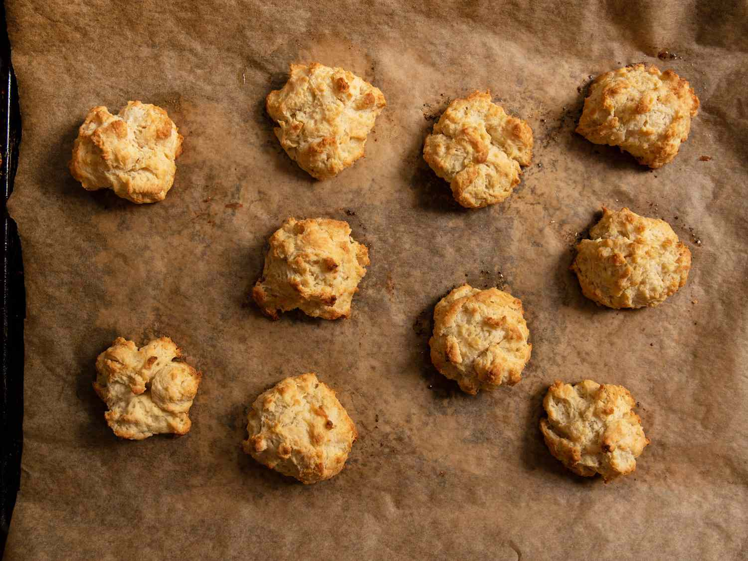 Baked drop biscuits on a parchment-lined baking sheet.