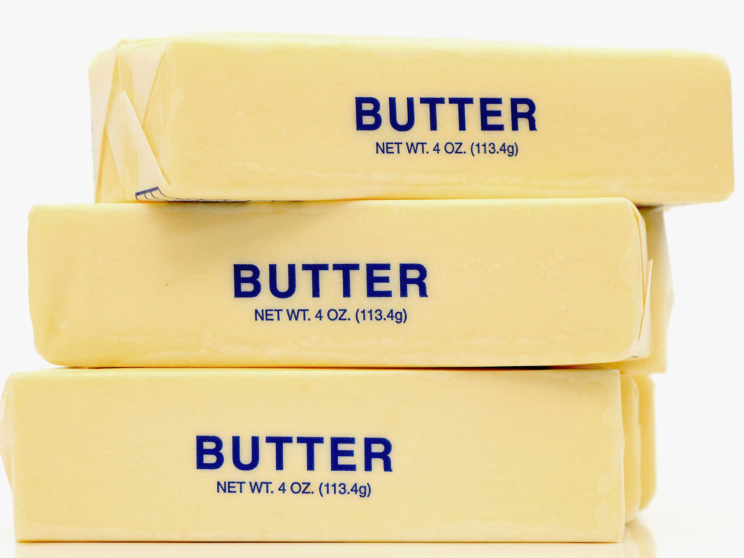 A stack of three sticks of butter in their wrappers.