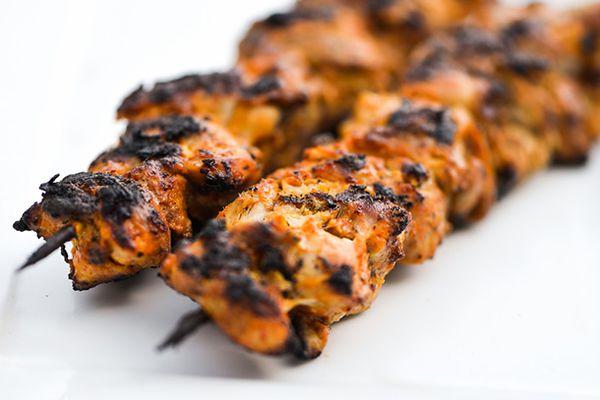 two skewers of smoky and spicy yogurt marinated chicken kebabs